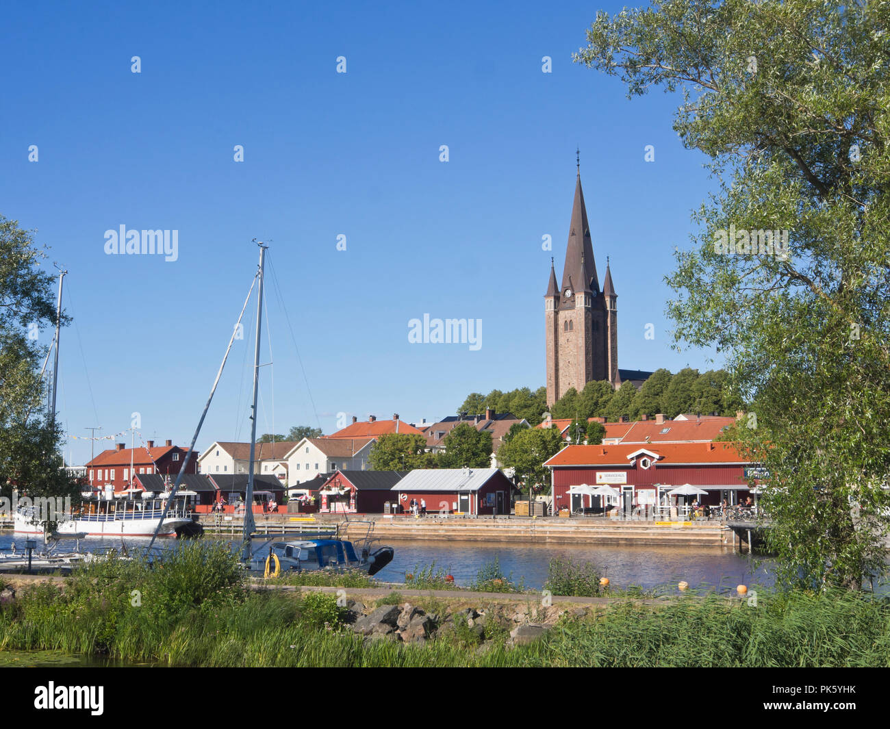 The harbour with restaurants and the cathedral spire in Mariestad, a picturesque town on the shore of Vaenern the largest lake in Sweden - Stock Image