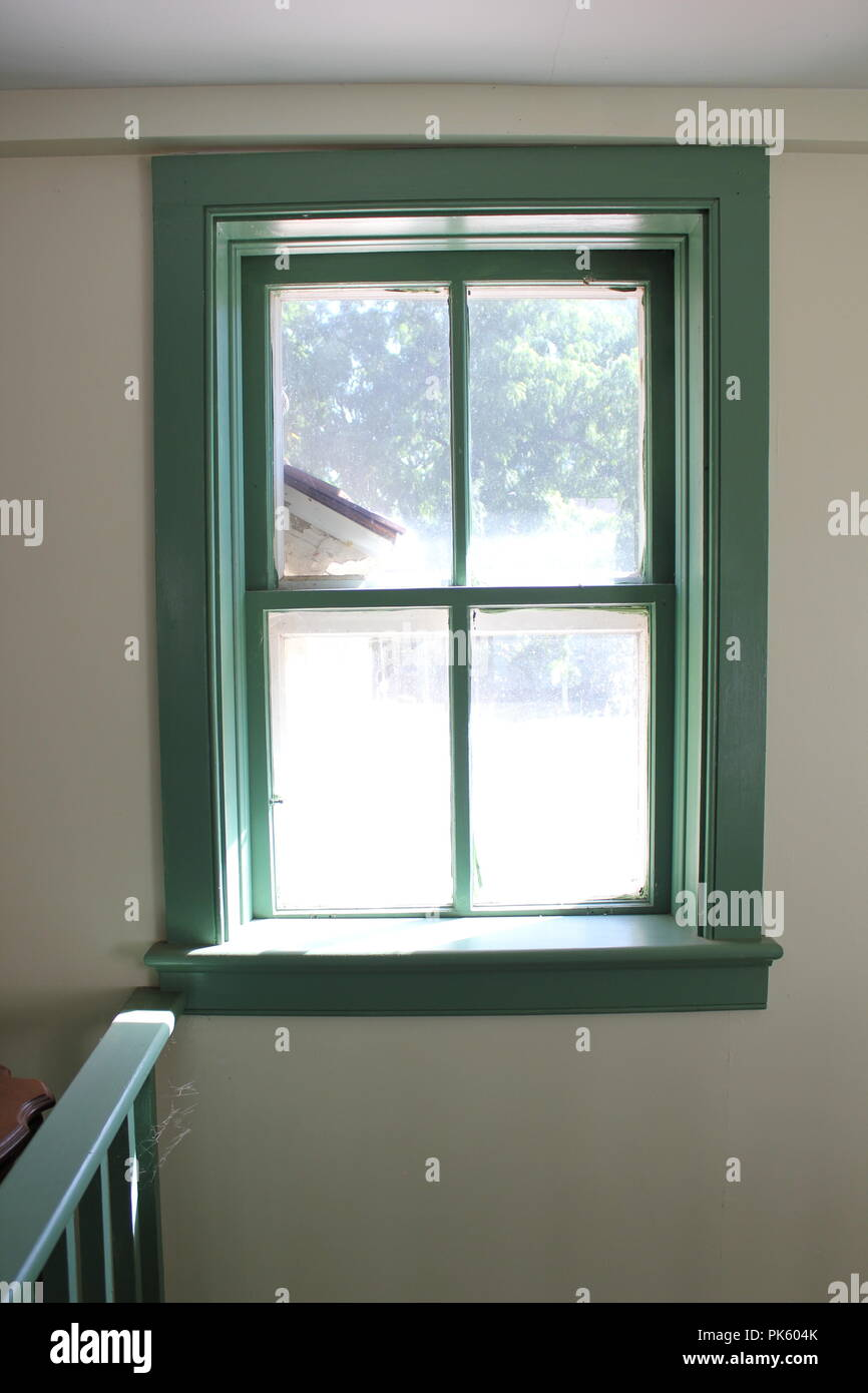 Wooden window painted green with a roof eave showing thru the view at the Volkening Heritage Farm in Schaumburg, Illinois on a late summer day. - Stock Image
