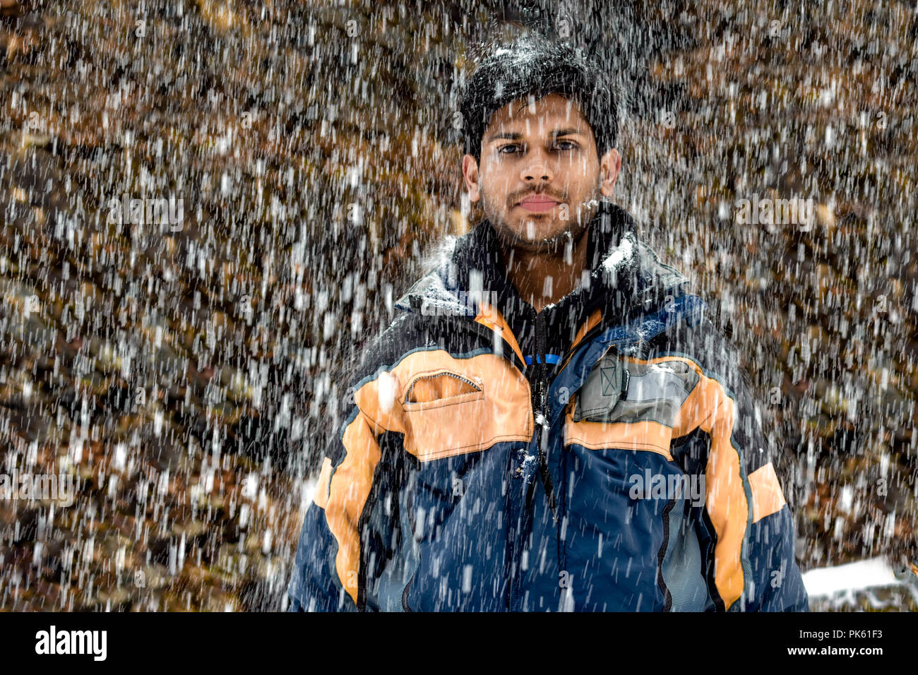 Young, Fair and Handsome Indian boy in early 20s in skiing costume, wearing snowsuit, standing still and posing in neutral mood during heavy snowfall - Stock Image