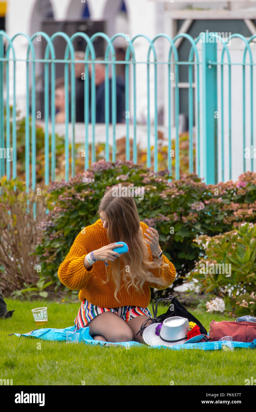 A festival goer relaxing at Festival Number 6 playing with her hair whilst sat down on a picnic mat, Portmeirion, Wales - Stock Image