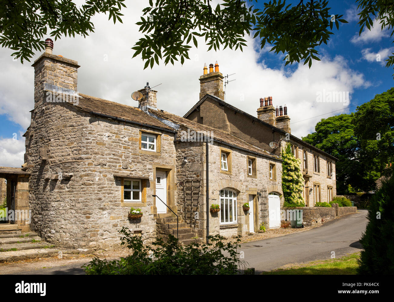 UK, Yorkshire, Horton in Ribblesdale, house with curved wall beside church lychgate Stock Photo