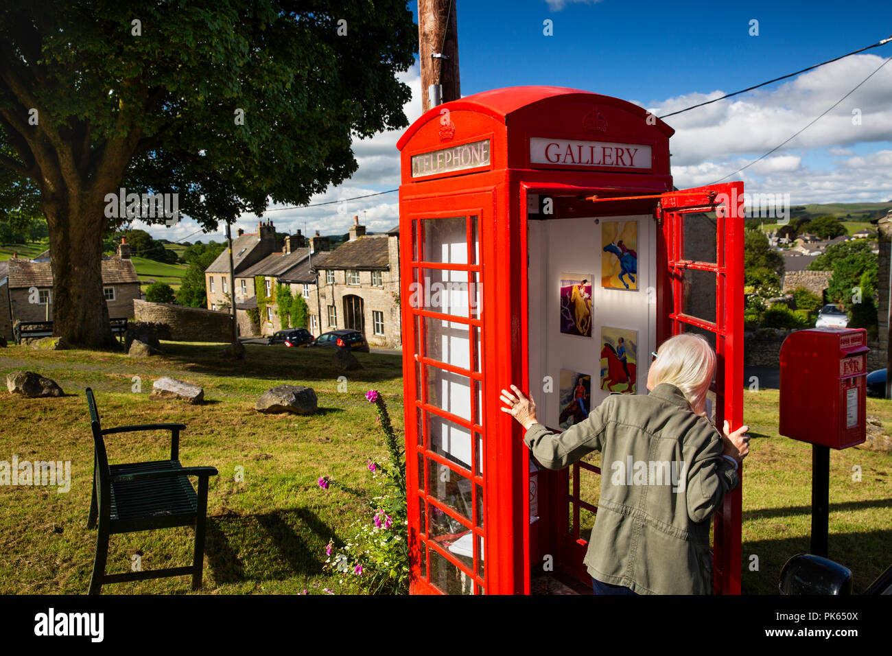 UK, Yorkshire, Settle, Green Head Lane, visitor looking into the Gallery on the Green, in old red K6 phone box, world's smnallest art gallery Stock Photo