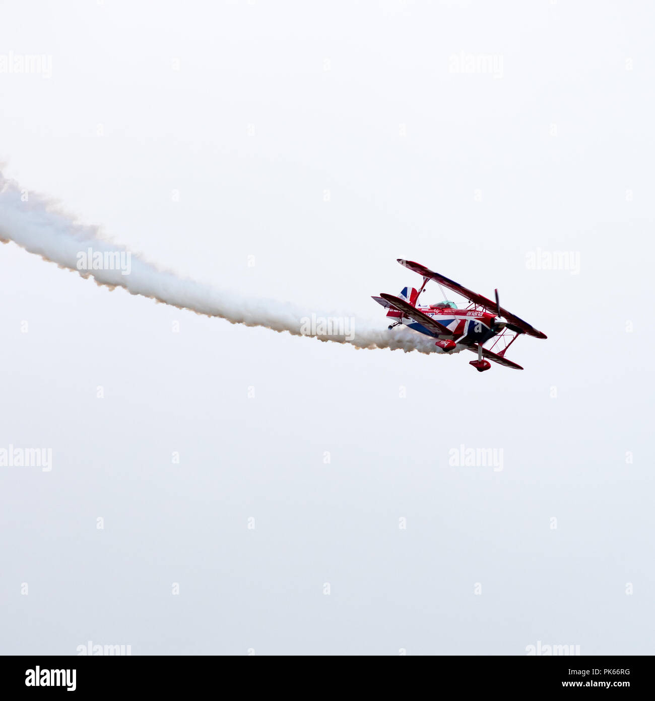 A highly modified Pitts Special S2S Biplane performing an aerobatics routine - Stock Image