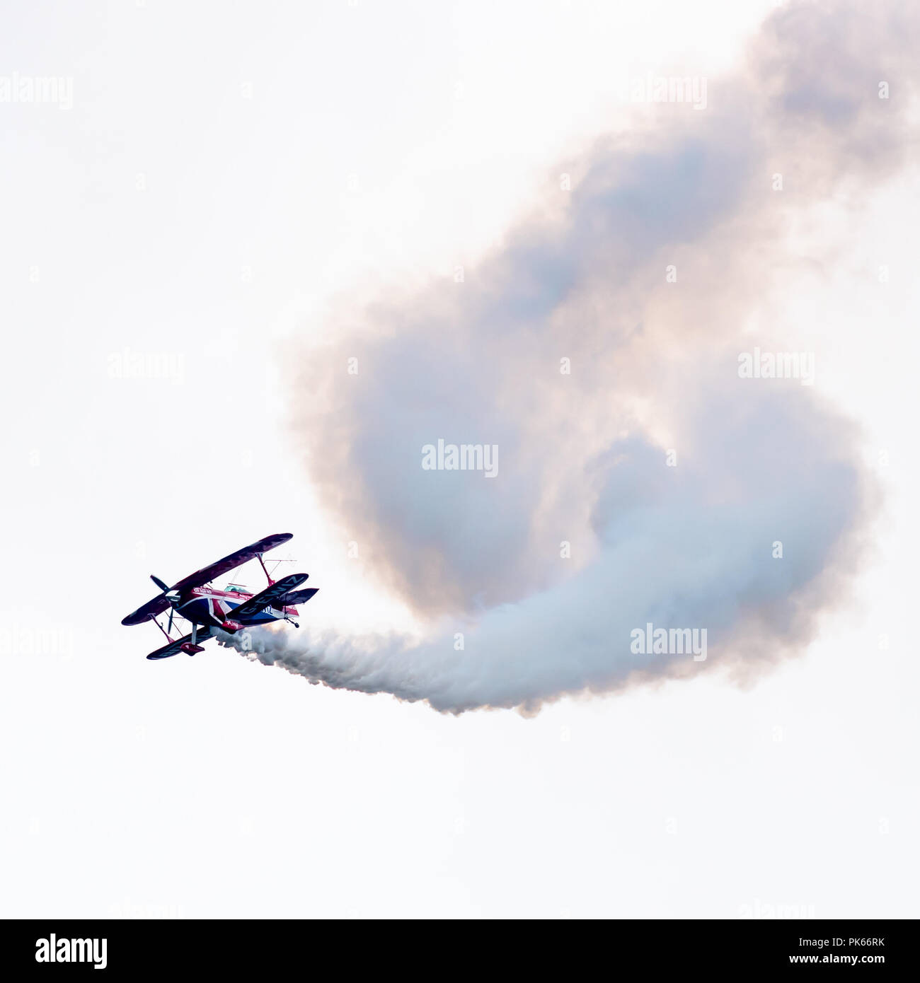 A corkscrew of white smoke billows behind Rich Goodwin's Pitts Special S2S biplane during an aerobatic display - Stock Image