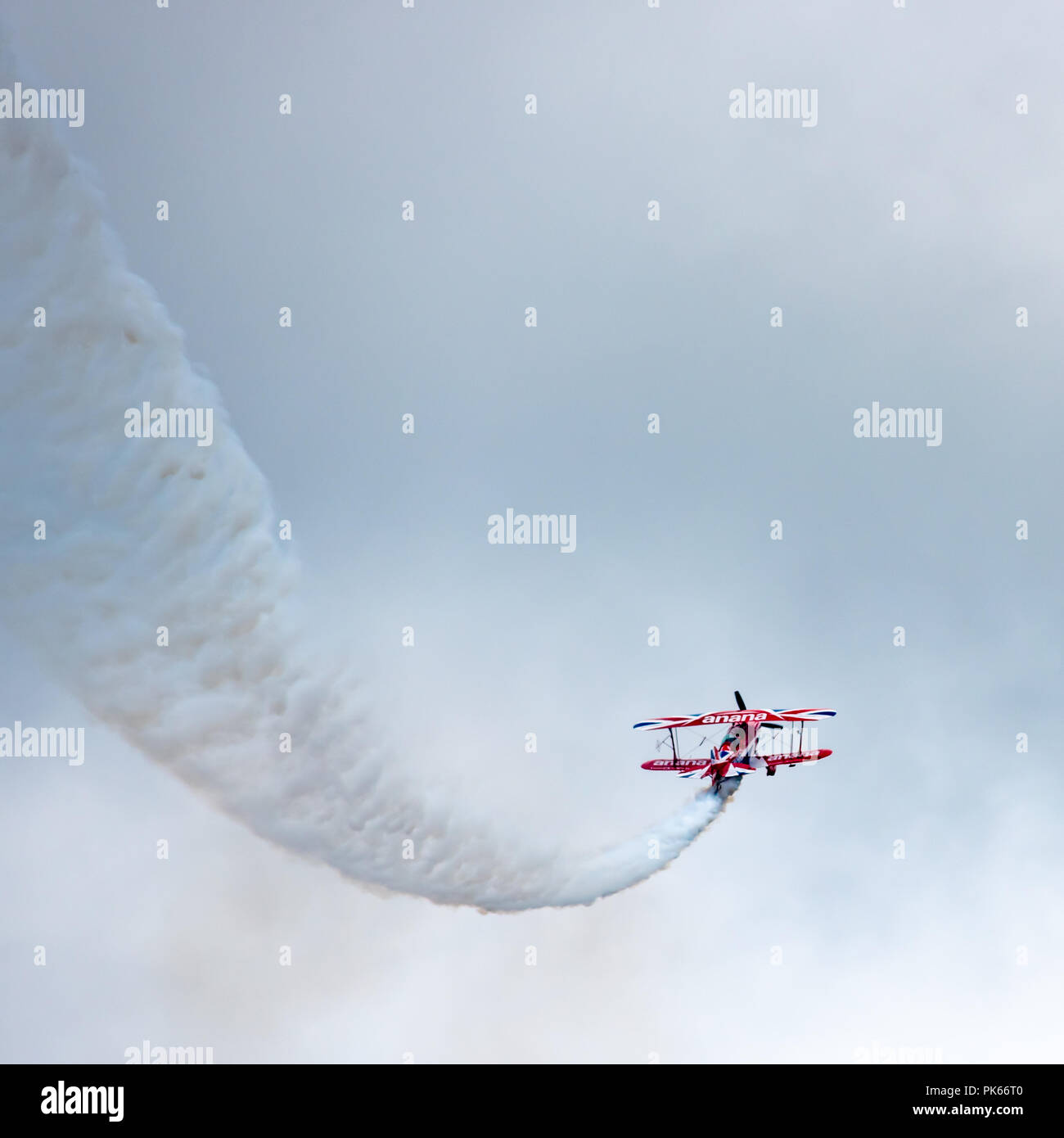 A Pitts Special S2S Biplane traces a path across a darkening sky - Stock Image