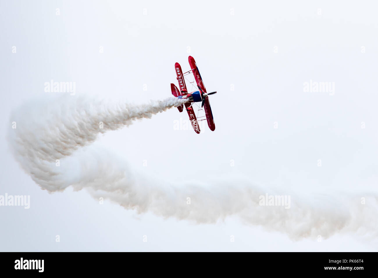 A Pitts Special S2S Biplane banks sharply leaving a curving plume of white smoke - Stock Image