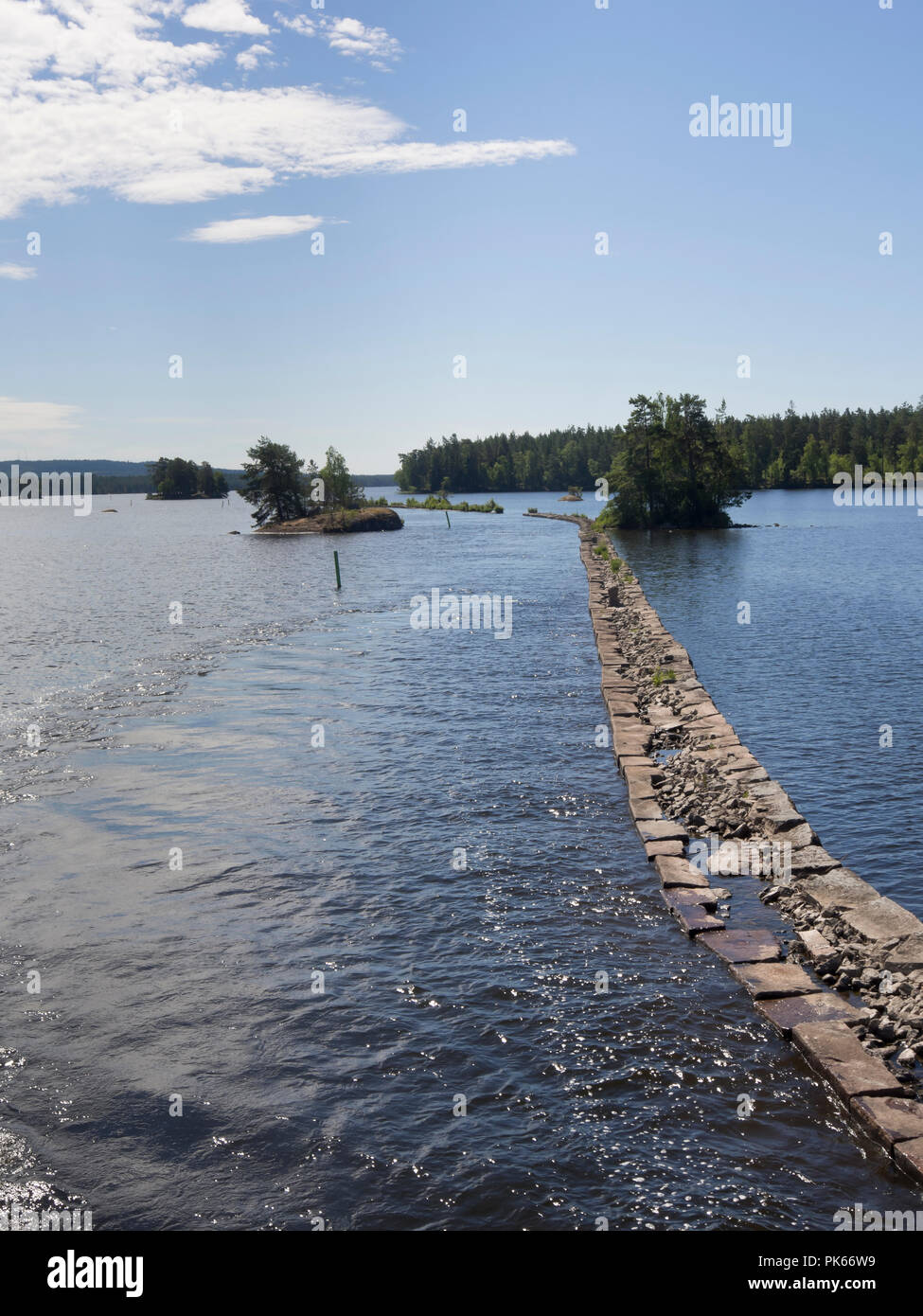 Stone wall built to guide the ships crossing the Viken lake on the Göta canal, boat cruise along an idyllic waterway in Sweden - Stock Image