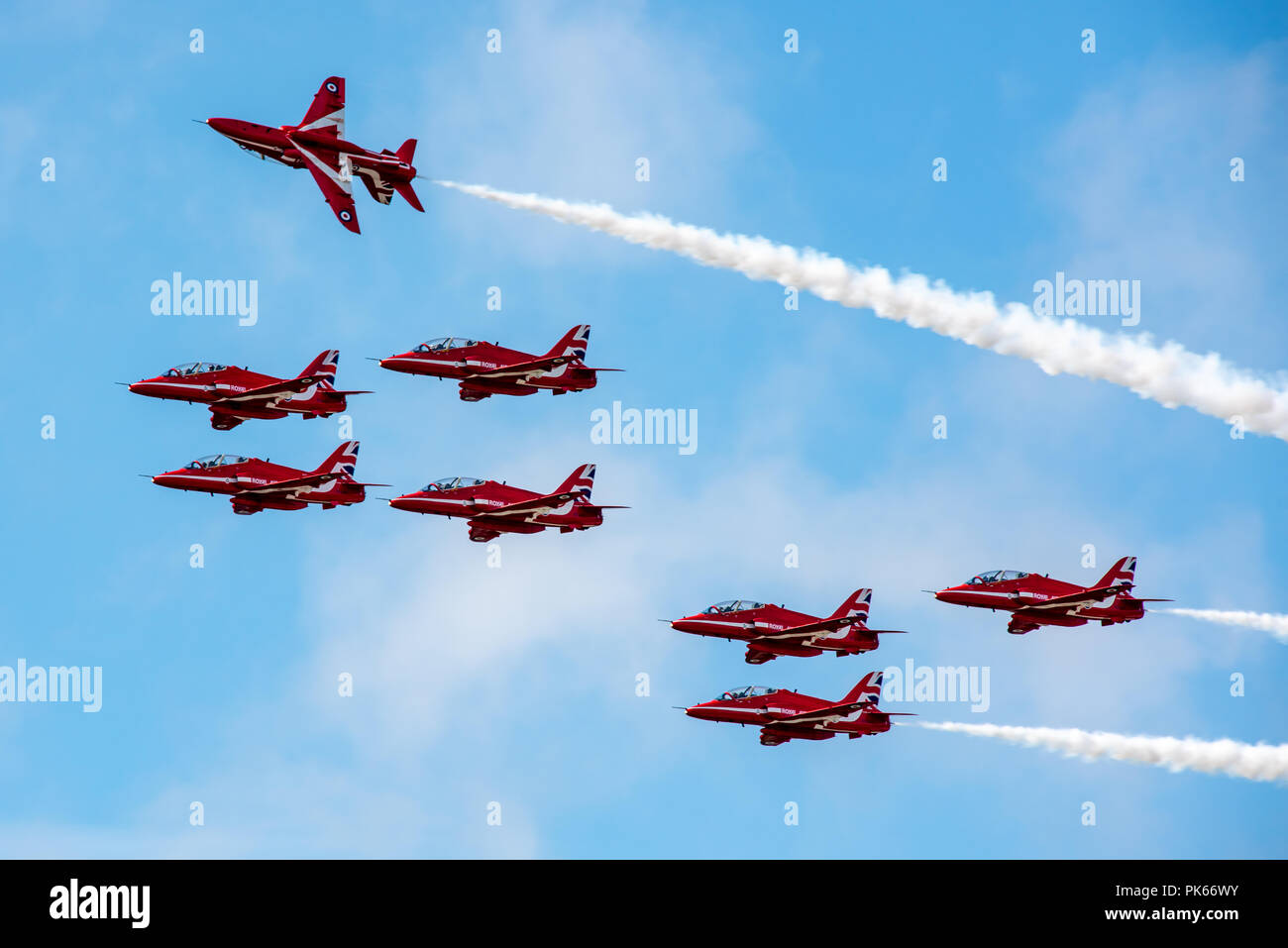 An RAF Red Arrows Hawk jet breaks formation and rolls above his team mates during a display manoeuvre - Stock Image