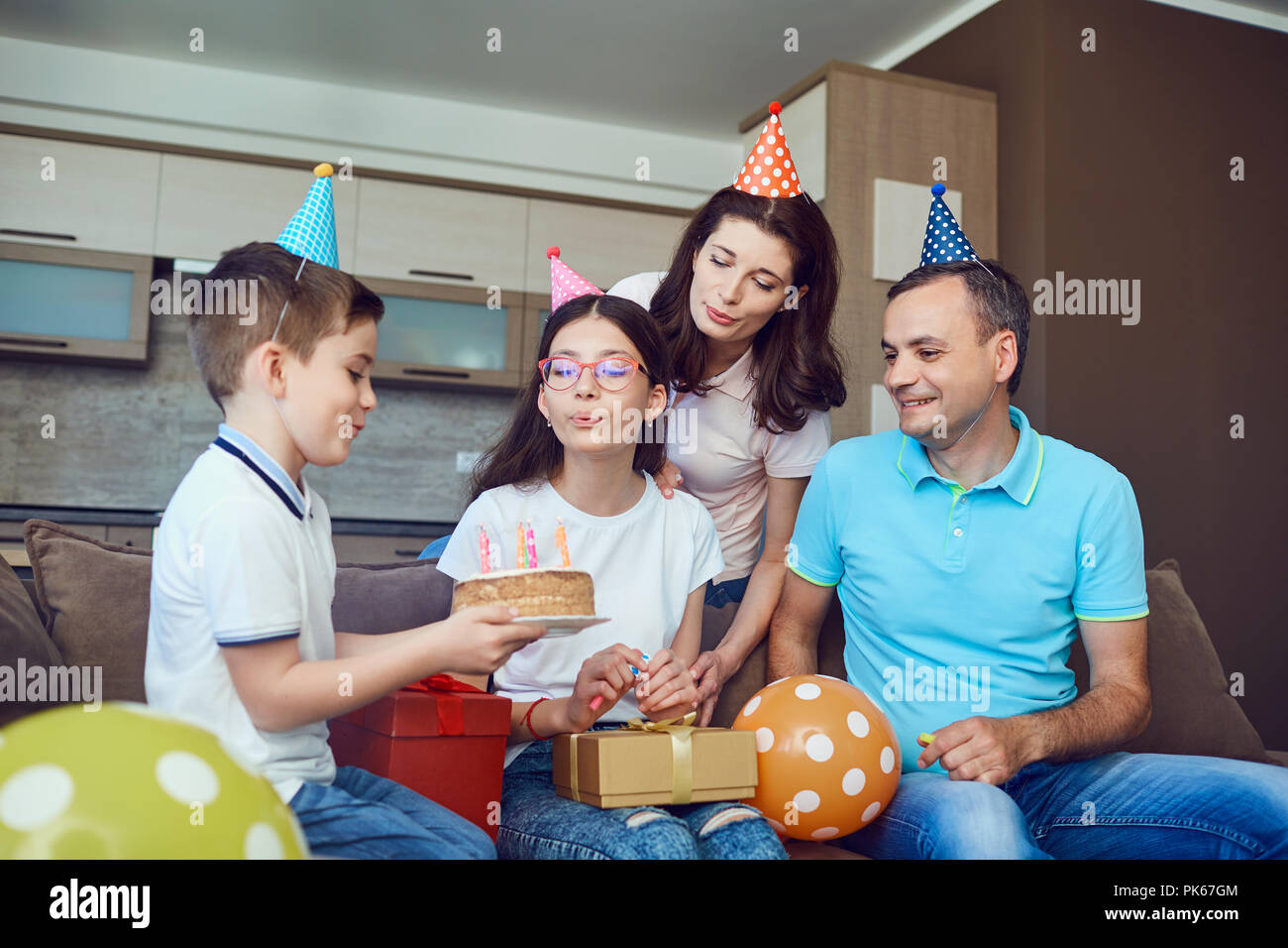 Family celebrates birthday with a birthday cake. Stock Photo