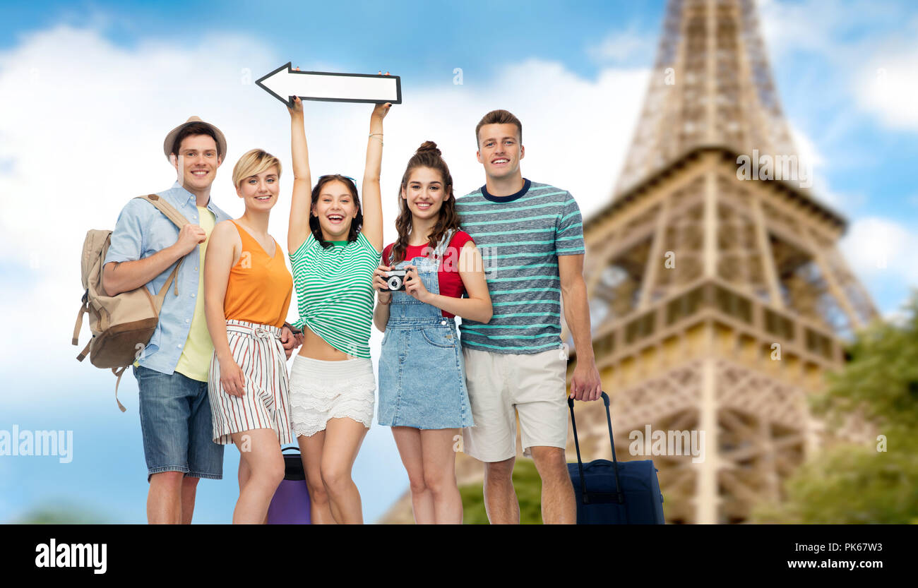friends with travel bags over eiffel tower - Stock Image