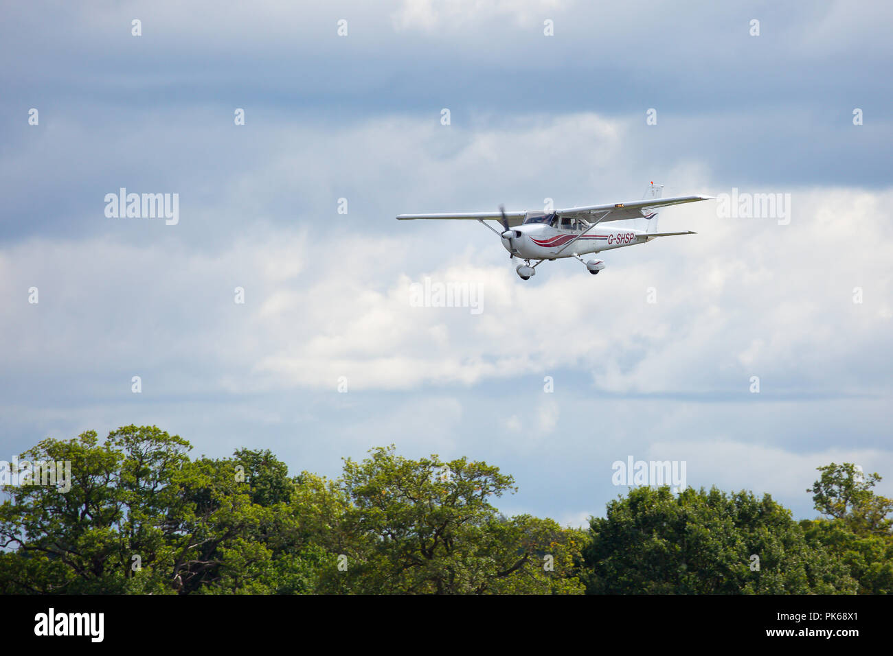 Landscape shot of a light aircraft, in the sky, coming in to land, UK. - Stock Image