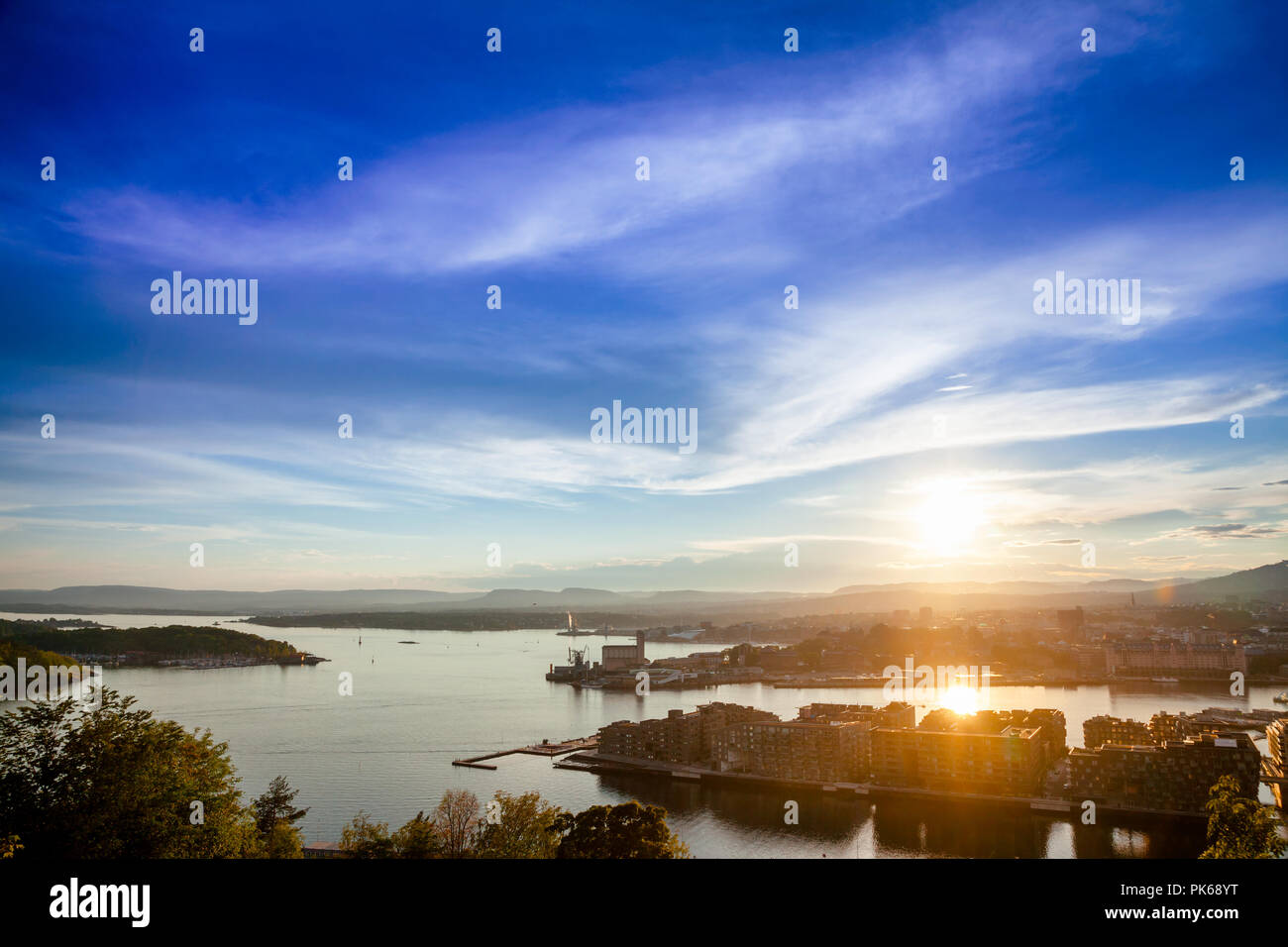 Oslo cityscape as viewed from the Ekeberg hill at sunset with sun reflecting in Oslofjord, Norway, Scandinavia - Stock Image