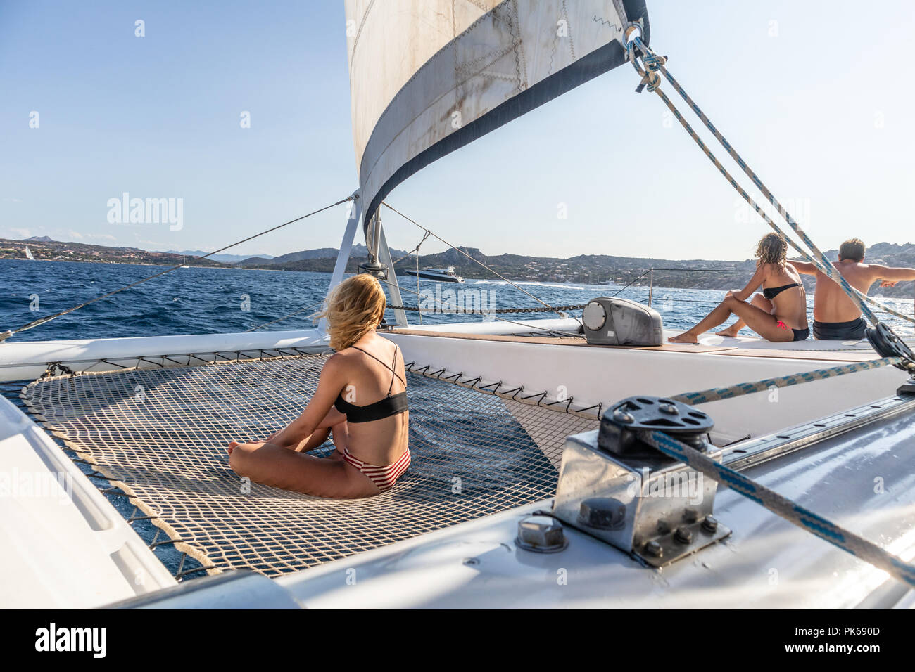 People relaxing on a summer sailing cruise, sitting on a luxury catamaran near picture perfect Palau town, Sardinia, Italy. Stock Photo