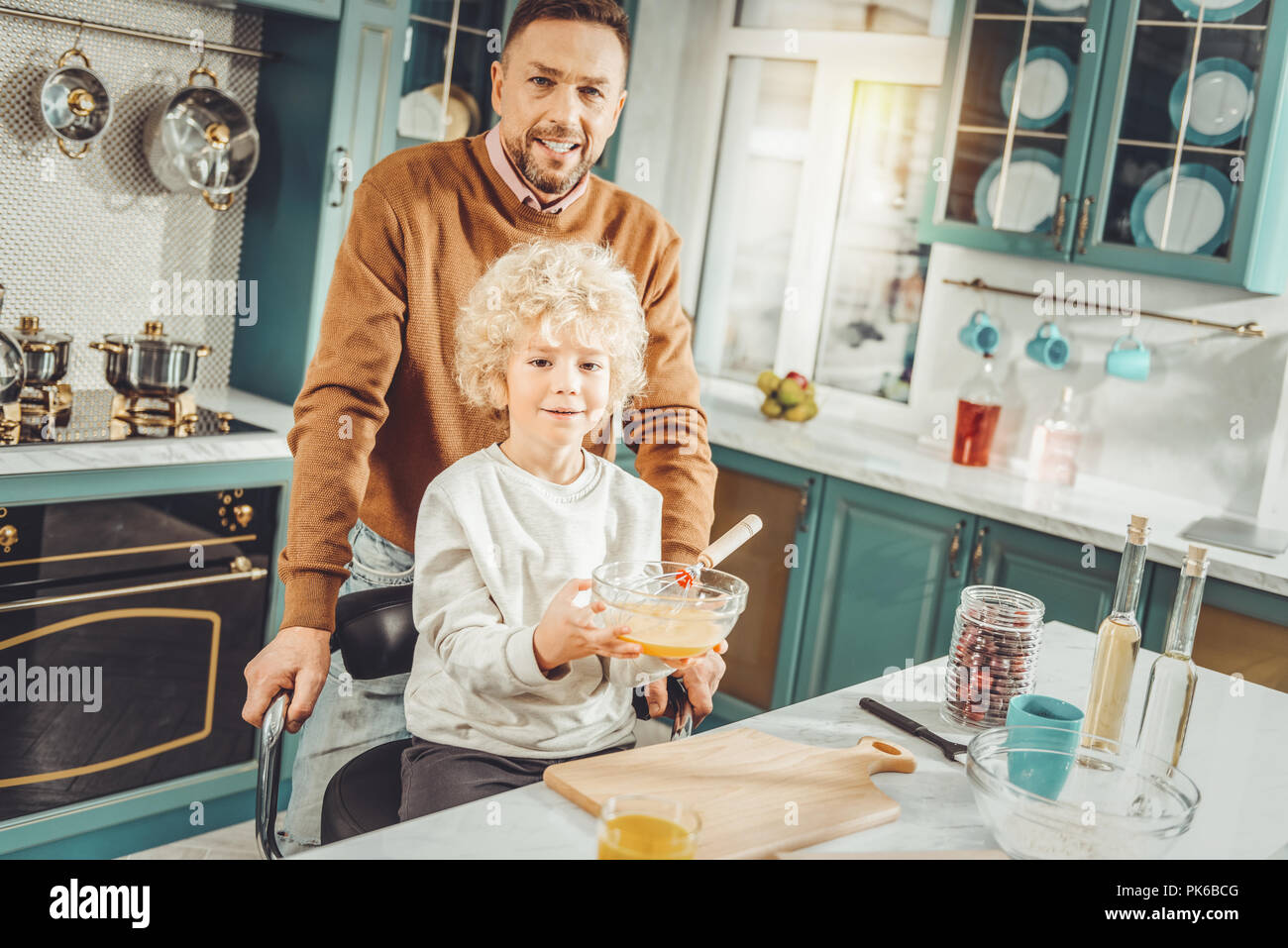 Curly blonde-haired boy holding bowl with whipped eggs - Stock Image