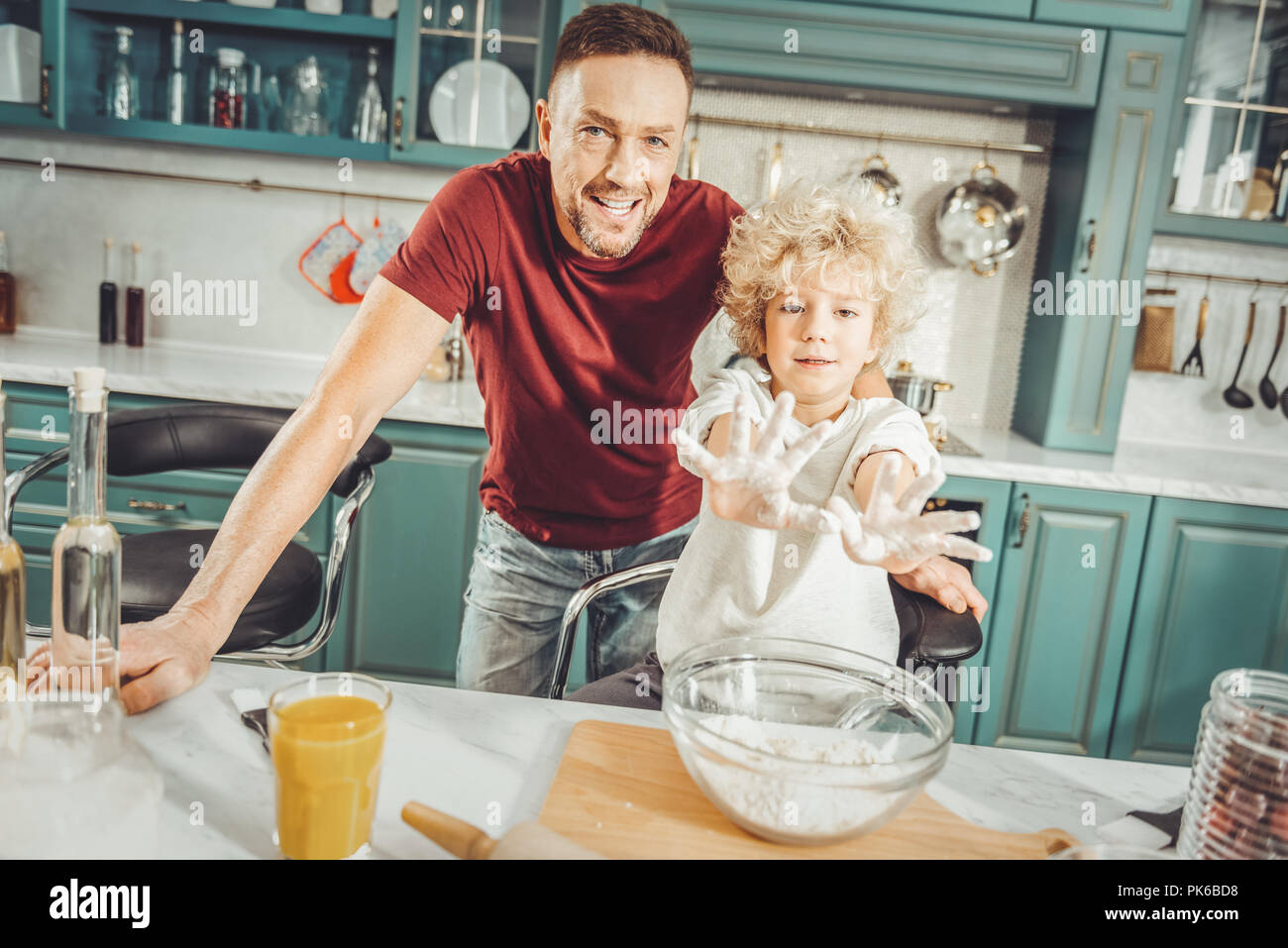 Curly blonde-haired boy showing his little hands in dough - Stock Image