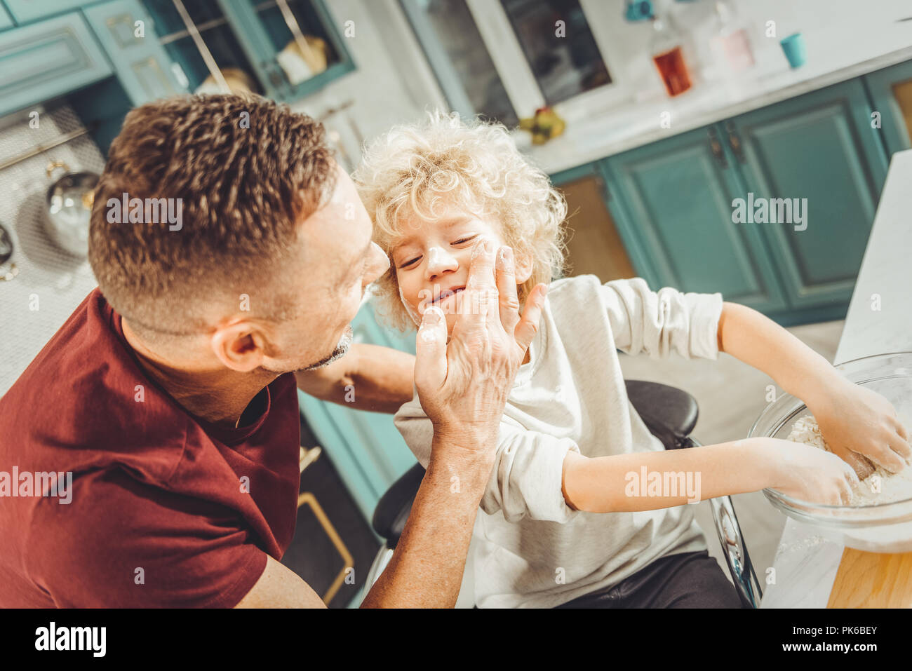 Curly blonde-haired boy feeling happy spending morning with father - Stock Image