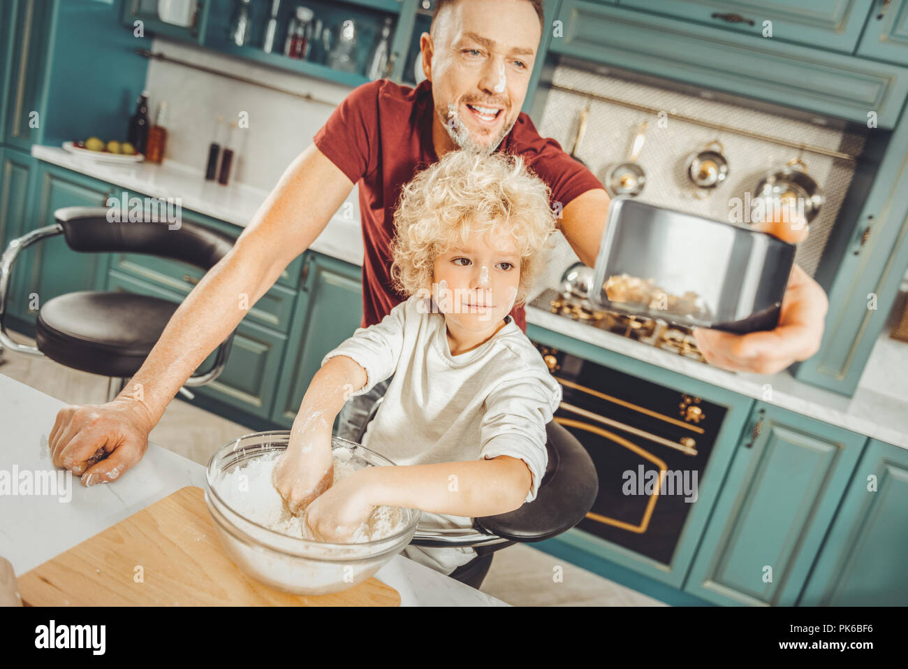 Dark-haired father making selfie with his little son cooking together - Stock Image
