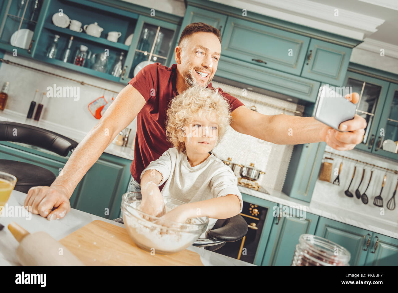 Father and son posing for selfie while making breakfast - Stock Image