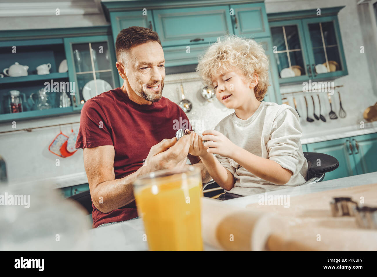 Curly blonde-haired boy giving baking rings his father - Stock Image
