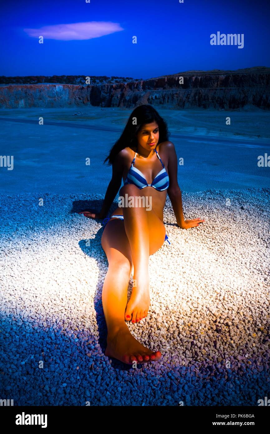 Creative night strong side light into pretty young woman weaing bikini swimsuit altered artistic rendition singularity shot - Stock Image
