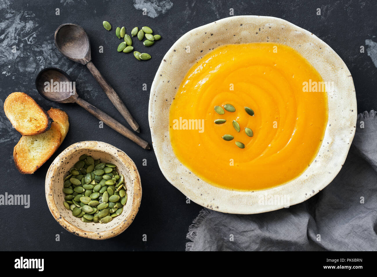 Pumpkin cream soup with toast and seeds on a rustic dark background. Top view, overhead, flat lay. Stock Photo