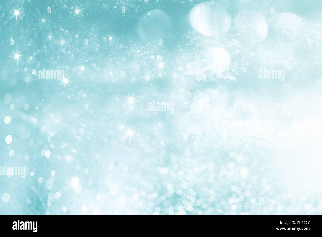 Turquoise abstract blurred sparkling christmas background with bokeh and asterisks - Stock Image