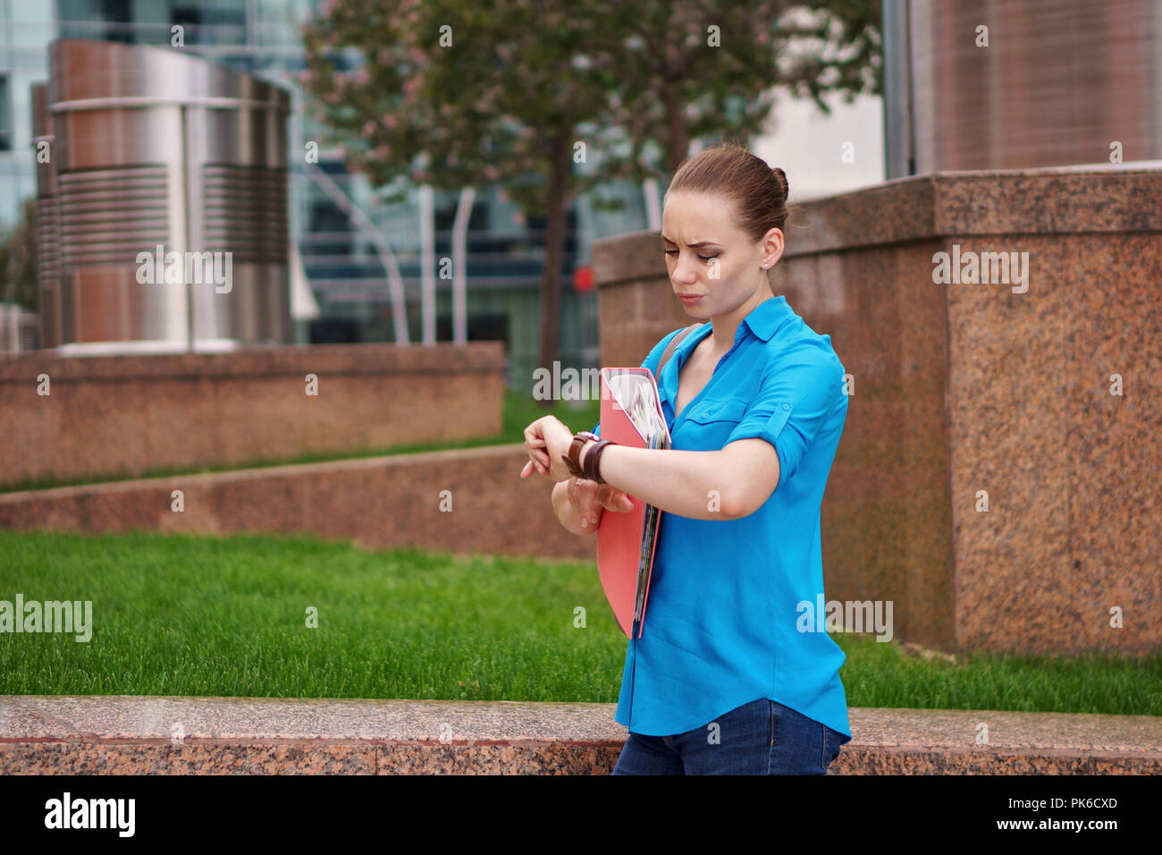 Young attractive girl is holding a folder for documents. The manager looks at the wristwatch. Late meeting - Stock Image