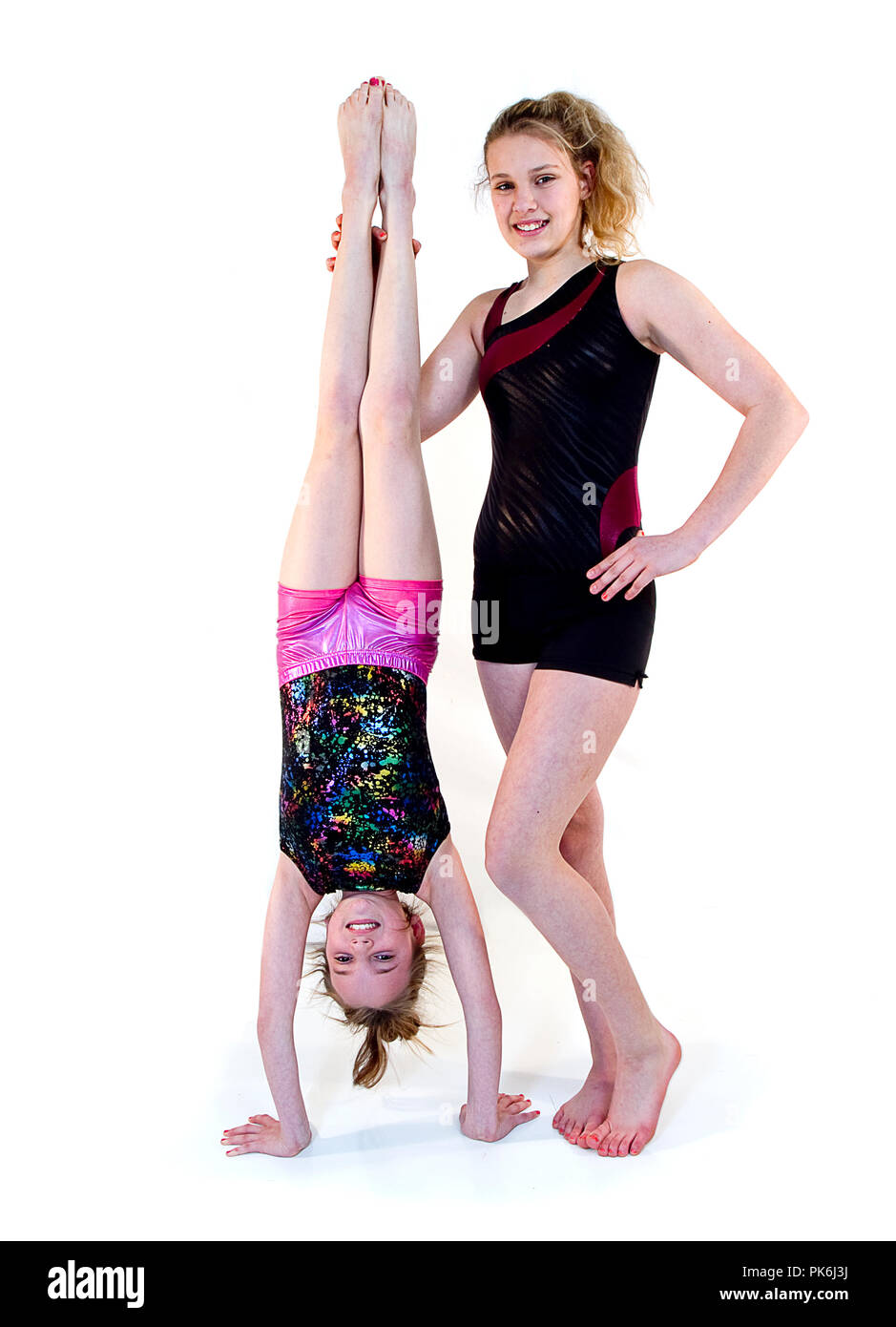Two beautiful young girls having fun working on their gymnastics.  Some individual images posing different positions and some where they work together. - Stock Image
