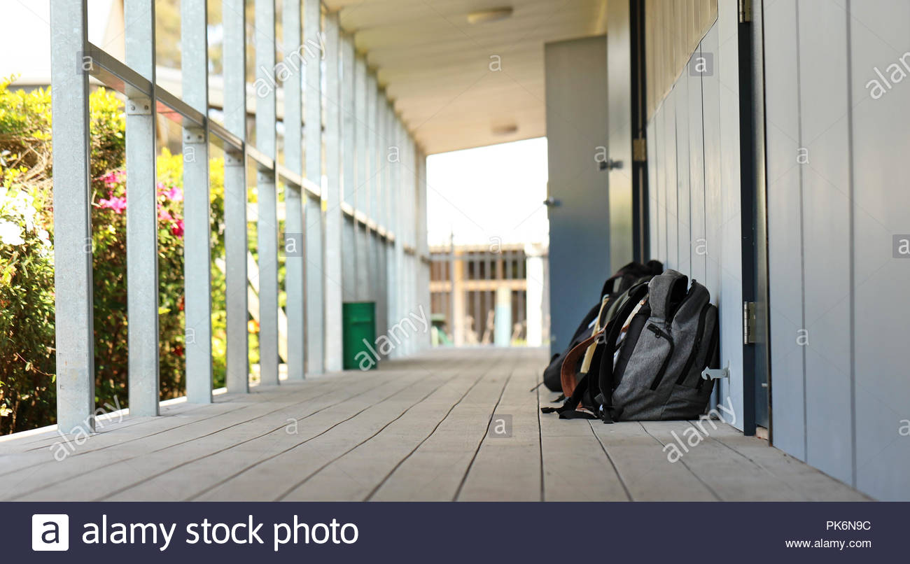 A number of school bags outside a classroom at high school. Long narrow hallway or outdoor corridor with bright sunshine. Educational theme or concept - Stock Image