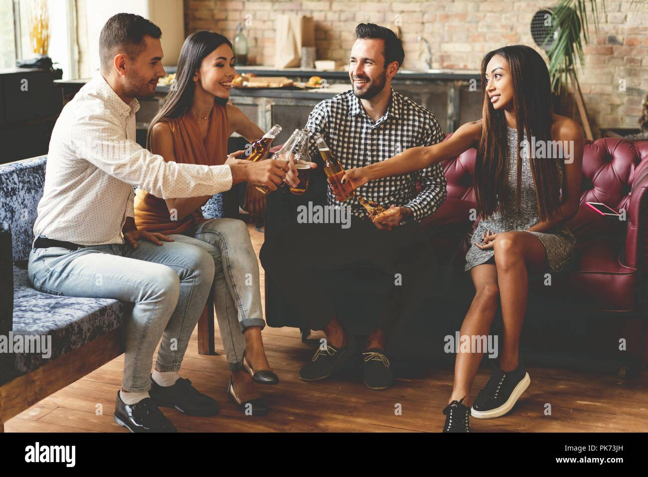 Spending great time with best friends. Group of cheerful young people enjoying food and drinks while spending nice time in cofortable chairs on the kitchen together. - Stock Image