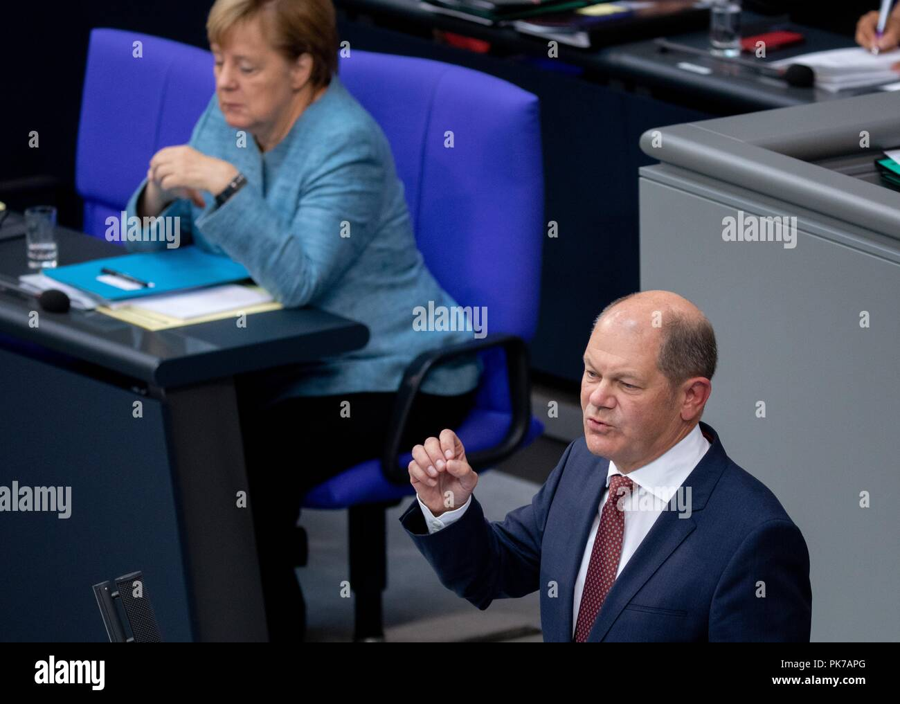 Berlin, Germany. 11 September 2018, Berlin: Olaf Scholz (SPD), Federal Minister of Finance, speaks at the plenary session in the German Bundestag, with Chancellor Angela Merkel (CDU) sitting in the background. The main topic of the 47th session of the 19th legislative period is the Federal Government's draft budget 2019 and the federal budget 2018 to 2022. Photo: Bernd von Jutrczenka/dpa Credit: dpa picture alliance/Alamy Live News - Stock Image