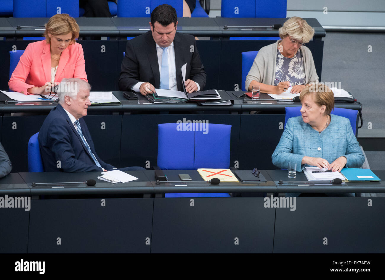 Berlin, Germany. 11 September 2018, Berlin: German Chancellor Angela Merkel (r, CDU) and Horst Seehofer (l, CSU), Federal Minister of the Interior, Home and Construction, will be talking during the plenary session in the German Bundestag. In the row behind it sit Julia Klöckner (CDU), Federal Minister for Food and Agriculture, Hubertus Heil (SPD), Federal Minister for Labour and Social Affairs, and Monika Grütters (CDU), Minister of State for Culture and the Media. The main topic of the 47th session of the 19th legislative period is the Federal Government's draft budget 2019 and the federal bu - Stock Image