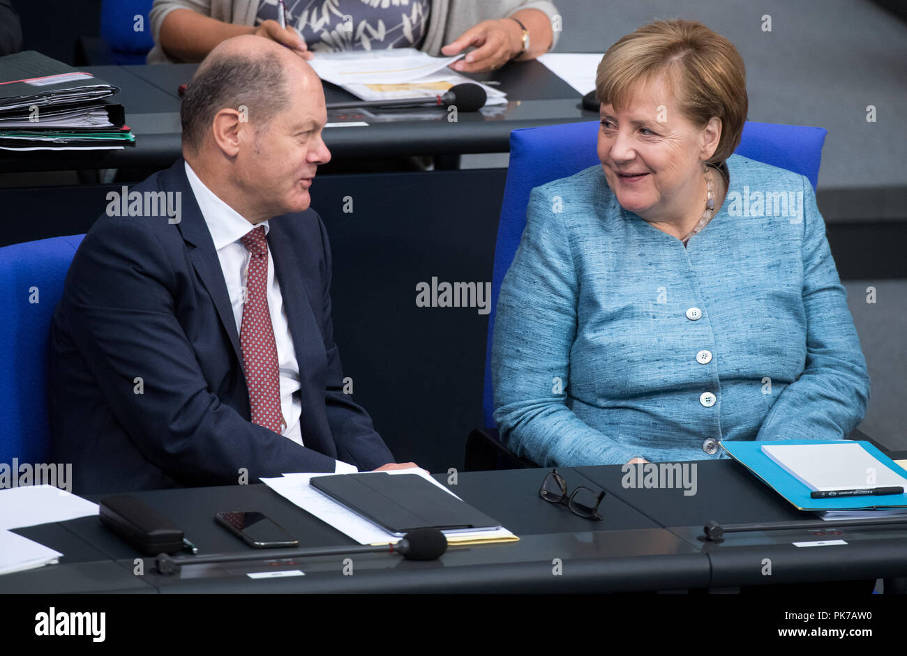 Berlin, Germany. 11 September 2018, Berlin: Chancellor Angela Merkel (r, CDU) and Olaf Scholz (SPD), Federal Minister of Finance, will talk during the plenary session in the German Bundestag. The main topic of the 47th session of the 19th legislative period is the Federal Government's draft budget 2019 and the federal budget 2018 to 2022. Photo: Bernd von Jutrczenka/dpa Credit: dpa picture alliance/Alamy Live News - Stock Image