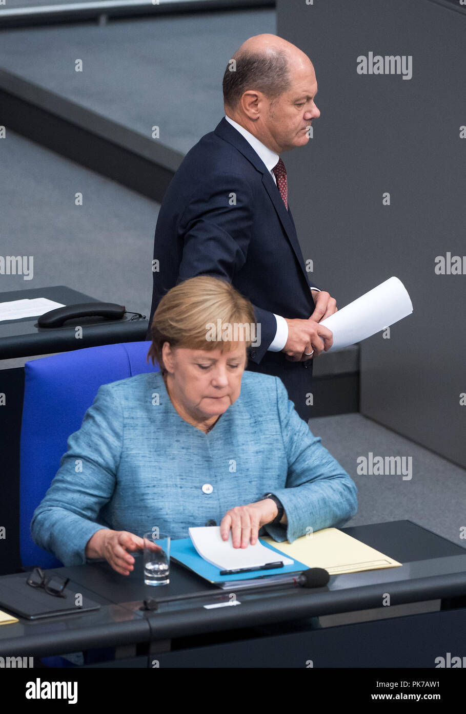 Berlin, Germany. 11 September 2018, Berlin: Olaf Scholz (SPD), Federal Minister of Finance, passes Chancellor Angela Merkel (CDU) to the lectern during the plenary session in the German Bundestag. The main topic of the 47th session of the 19th legislative period is the Federal Government's draft budget 2019 and the federal budget 2018 to 2022. Photo: Bernd von Jutrczenka/dpa Credit: dpa picture alliance/Alamy Live News - Stock Image