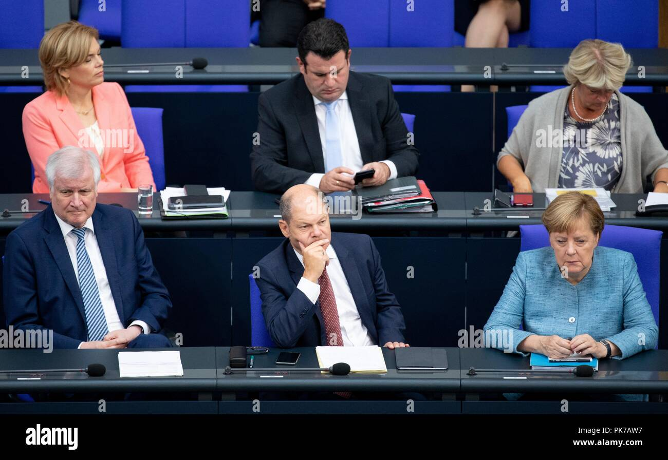 Berlin, Germany. 11 September 2018, Berlin: Horst Seehofer (front l-r, CSU), Federal Minister of the Interior, for Building and Home Affairs, Olaf Scholz (SPD), Federal Minister of Finance, and Chancellor Angela Merkel (CDU) will attend the plenary session in the German Bundestag. The main topic of the 47th session of the 19th legislative period is the Federal Government's draft budget 2019 and the federal budget 2018 to 2022. Photo: Bernd von Jutrczenka/dpa Credit: dpa picture alliance/Alamy Live News - Stock Image