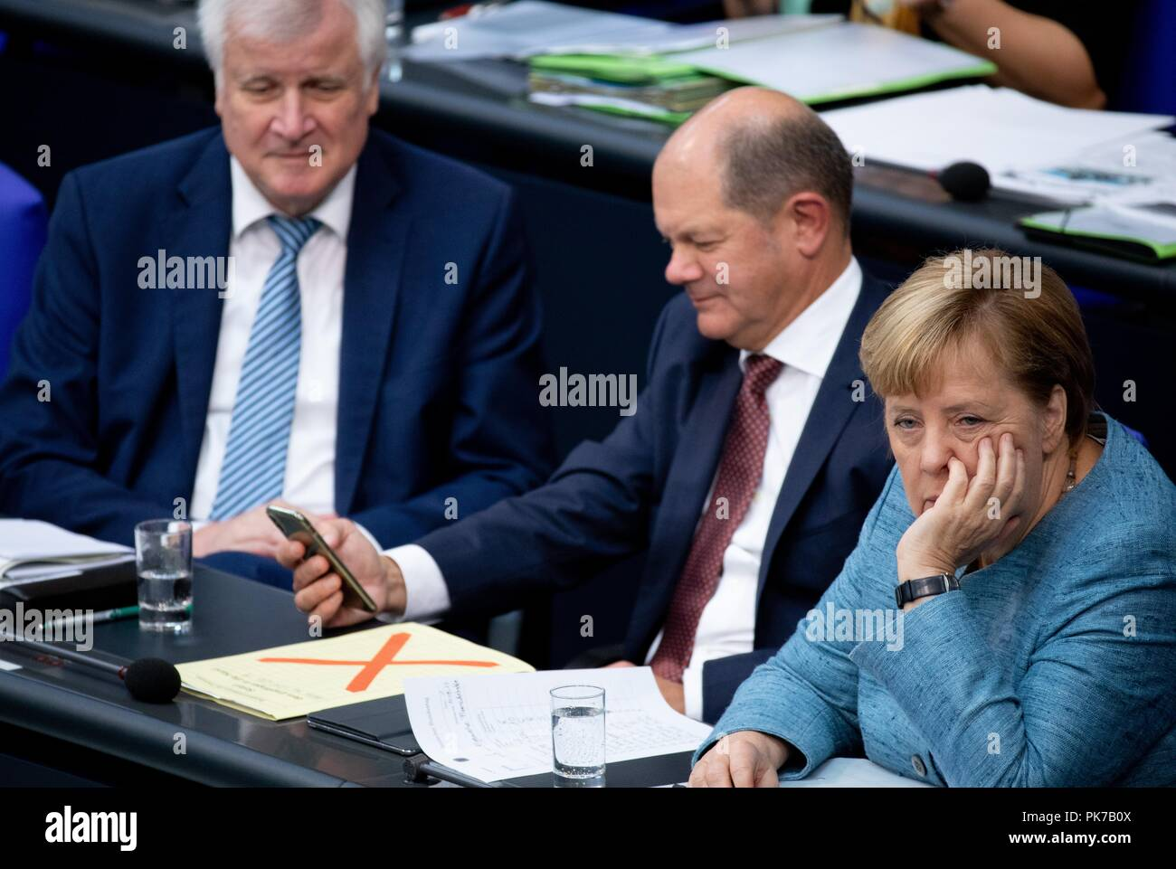 Berlin, Germany. 11 September 2018, Berlin: Horst Seehofer (l-r, CSU), Federal Minister of the Interior, for Building and Home Affairs, Olaf Scholz (SPD), Federal Minister of Finance, and Chancellor Angela Merkel (CDU) will attend the plenary session in the German Bundestag. The main topic of the 47th session of the 19th legislative period is the Federal Government's draft budget 2019 and the federal budget 2018 to 2022. Photo: Bernd von Jutrczenka/dpa Credit: dpa picture alliance/Alamy Live News - Stock Image