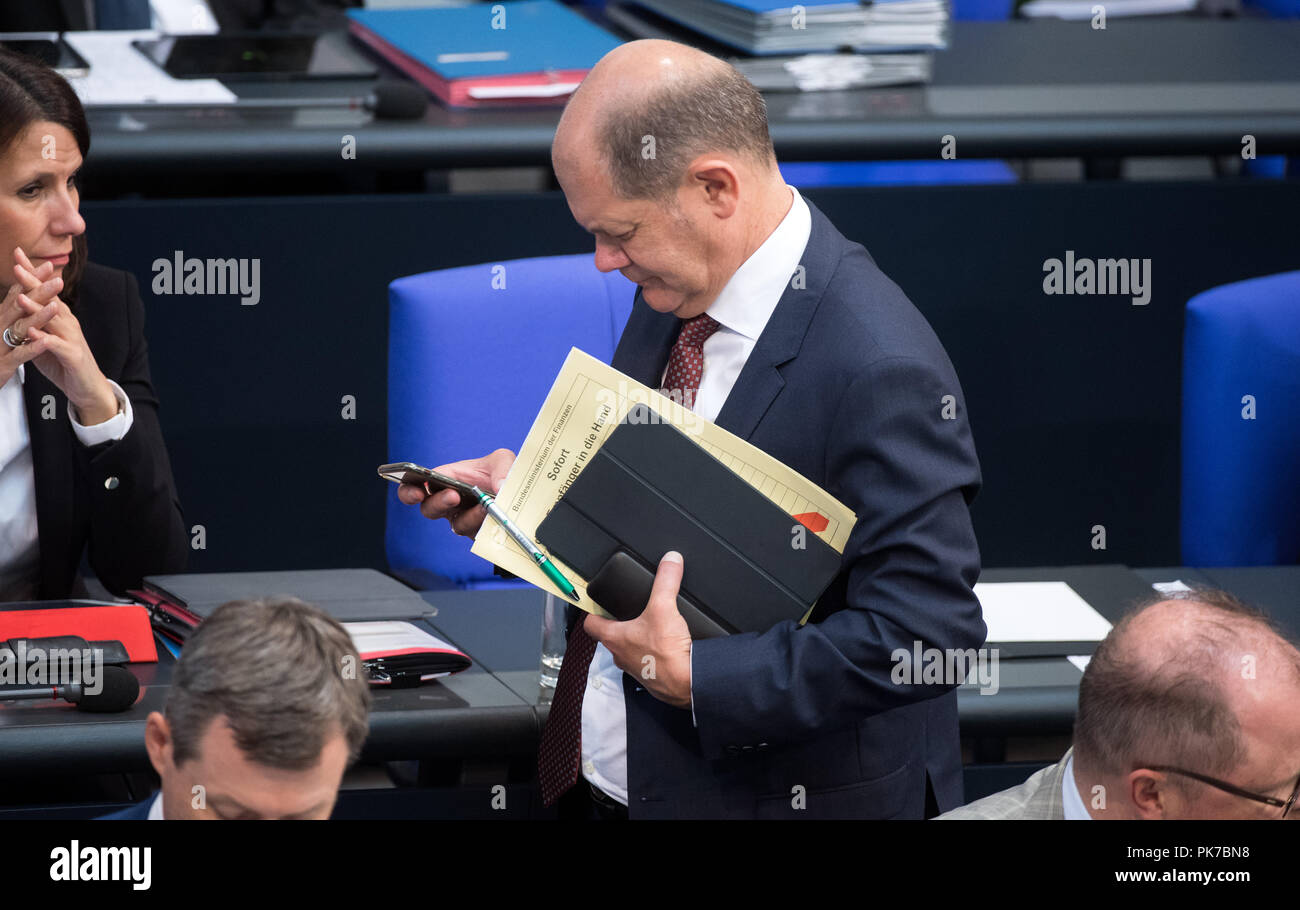 Berlin, Germany. 11 September 2018, Berlin: Olaf Scholz (SPD), Federal Minister of Finance, looks at his mobile phone as he leaves the plenary session in the German Bundestag. The main topic of the 47th session of the 19th legislative period is the Federal Government's draft budget 2019 and the federal budget 2018 to 2022. Photo: Bernd von Jutrczenka/dpa Credit: dpa picture alliance/Alamy Live News - Stock Image