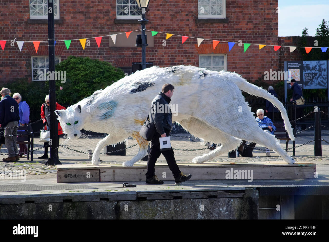 LIVERPOOL, UK. 11 September 2018. Visitors at Liverpool's Albert Dock enjoy the sunshine near the 'Ship's Cat' a fifteen foot-long art installation by Liverpool artist Faith Bebbington, who creates hand-built, dynamic figurative sculptures of animals, using recycled waste materials. Inspired by legendary feline seafarers like Ms Chibley, who circumnavigated the globe as chief rodent control officer on the tall ship Picton Castle.  Premos/Alamy Live News - Stock Image