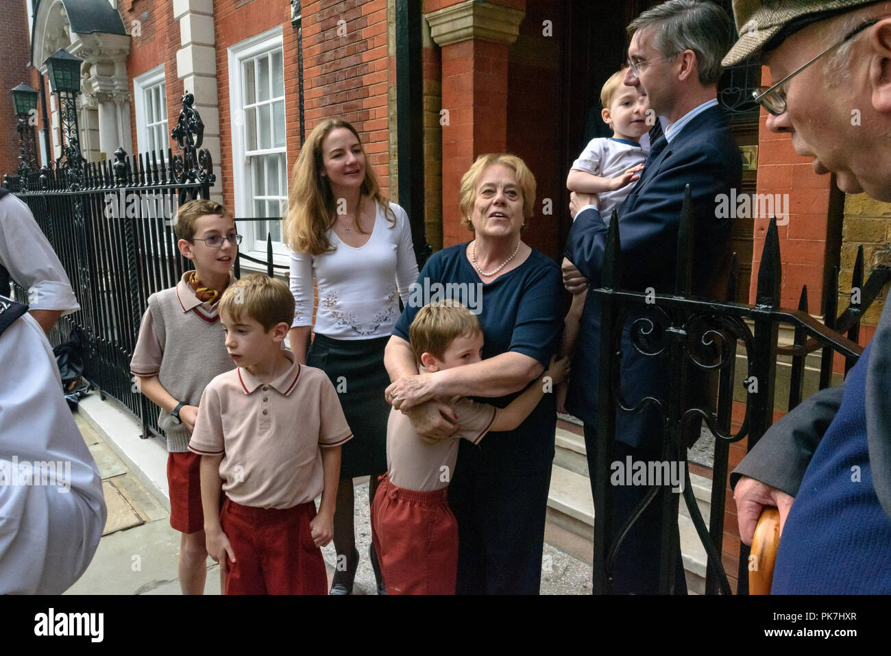 London, UK. 11th Sept 2018. Jacob Rees-Mogg with his wife, Nanny Cook and four of his six children as Ian Bone of Class War speaks to them outside his £5.6m Westminster town house calling for the release of Veronica Cook, who now looks after him and his six children, one of whom stands with his wife watching. They say she ceased to exist as an independent human 50 years ago and has been subsumed into the Mogg family as if she was being confined in the tower of a gothic mansion. The protest starred former Class War Westminster candidate Adam Clifford as Jacob Rees-Mogg and Jane Nicholl as NannyStock Photo