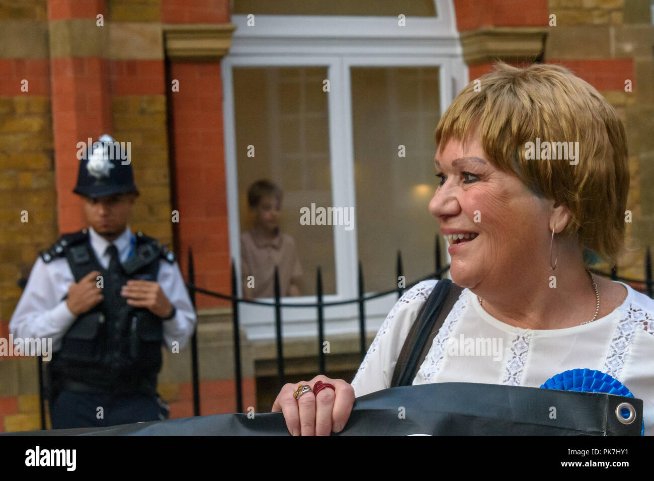 London, UK. 11th Sept 2018. One of the Rees-Mogg children watches from the window as Class War protest  at the £5.6m Westminster town house of Jacob Rees-Mogg. Jane Nicholl is dressed as Nanny Cook, Jacob Rees-Mogg's nanny who now looks after him and his six children. They say she ceased to exist as an independent human 50 years ago and has been subsumed into the Mogg family as if she was being confined in the tower of a gothic mansion. The protest starred former Class War Westminster candidate Adam Clifford as Jacob Rees-Mogg and Jane Nicholl as Nanny Crook, as well as a giant penis and offerStock Photo