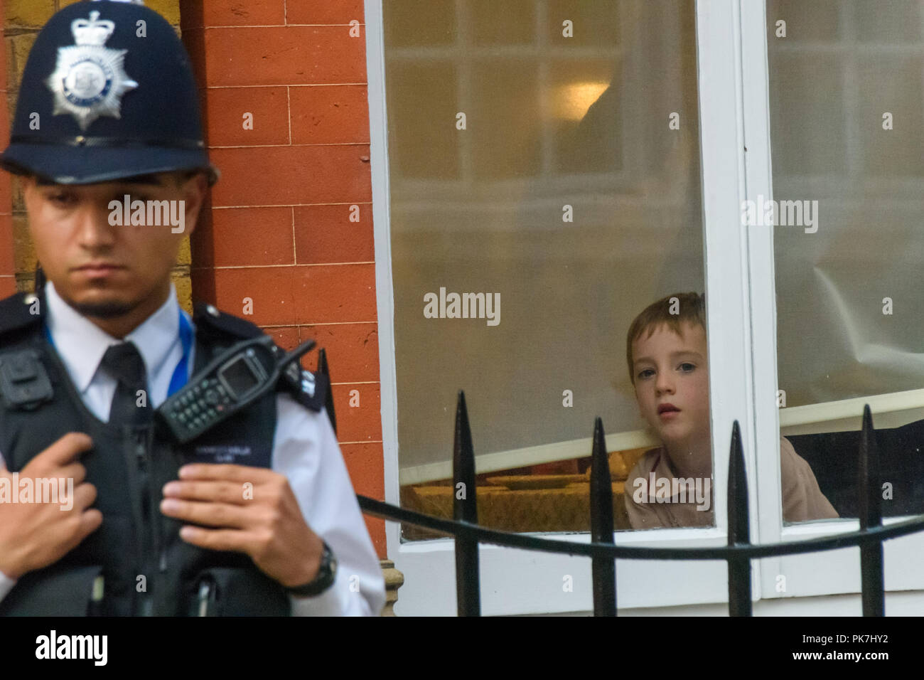 London, UK. 11th Sept 2018. One of the Rees-Mogg children watches from the window as Class War protest at the £5.6m Westminster town house of Jacob Rees-Mogg. Class War say Nanny Cook, Jacob Rees-Mogg's nanny who now looks after him and his six children, ceased to exist as an independent human 50 years ago and has been subsumed into the Mogg family as if she was being confined in the tower of a gothic mansion. The protest starred former Class War Westminster candidate Adam Clifford as Jacob Rees-Mogg and Jane Nicholl as Nanny Crook, as well as a giant penis and offered escape to Veronica Cook, Stock Photo