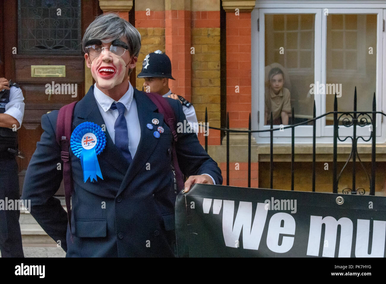 London, UK. 11th Sept 2018. One of the Rees-Mogg children watches from the window as Adam Clifford, dressed as Jacob Rees-Mogg, holds a banner at the Class War protest  at his £5.6m Westminster town house of Jacob Rees-Mogg. Class War say Nanny Cook, Jacob Rees-Mogg's nanny who now looks after him and his six children, ceased to exist as an independent human 50 years ago and has been subsumed into the Mogg family as if she was being confined in the tower of a gothic mansion. The protest starred former Class War Westminster candidate Adam Clifford as Jacob Rees-Mogg and Jane Nicholl as Nanny CrStock Photo