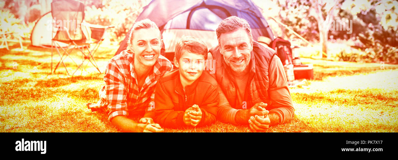 Father mother and son lying outside the tent at campsite - Stock Image