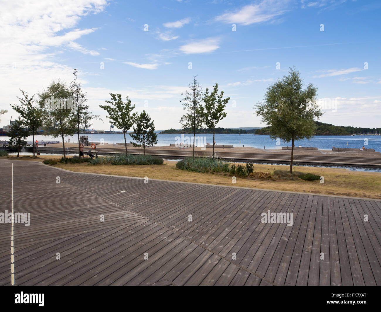 Beach and wooden sun-deck at Sorenga, the new residential neighborhood  in central Oslo Norway, early morning  on the Oslo fjord - Stock Image