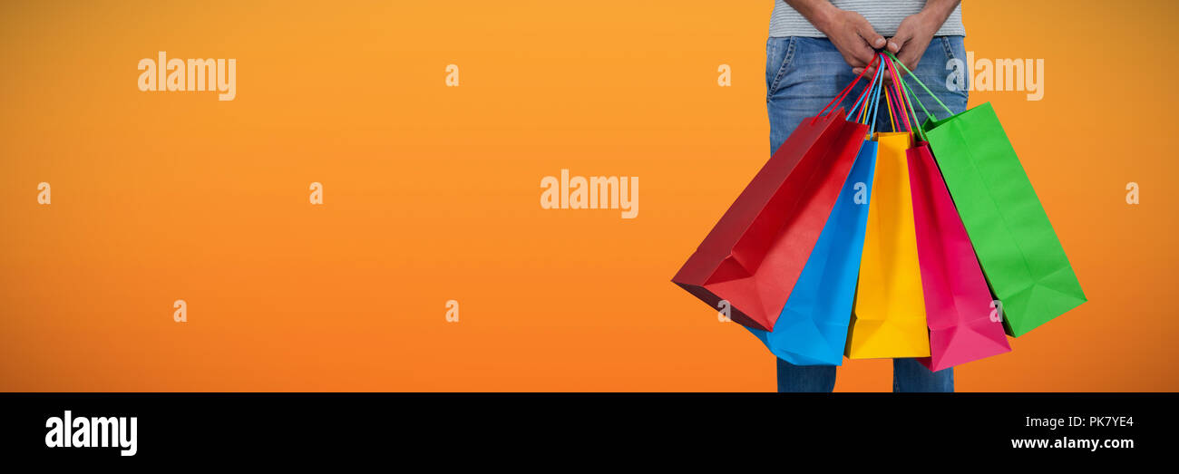 Composite image of low section of man carrying colorful shopping bag standing against white backgrou - Stock Image