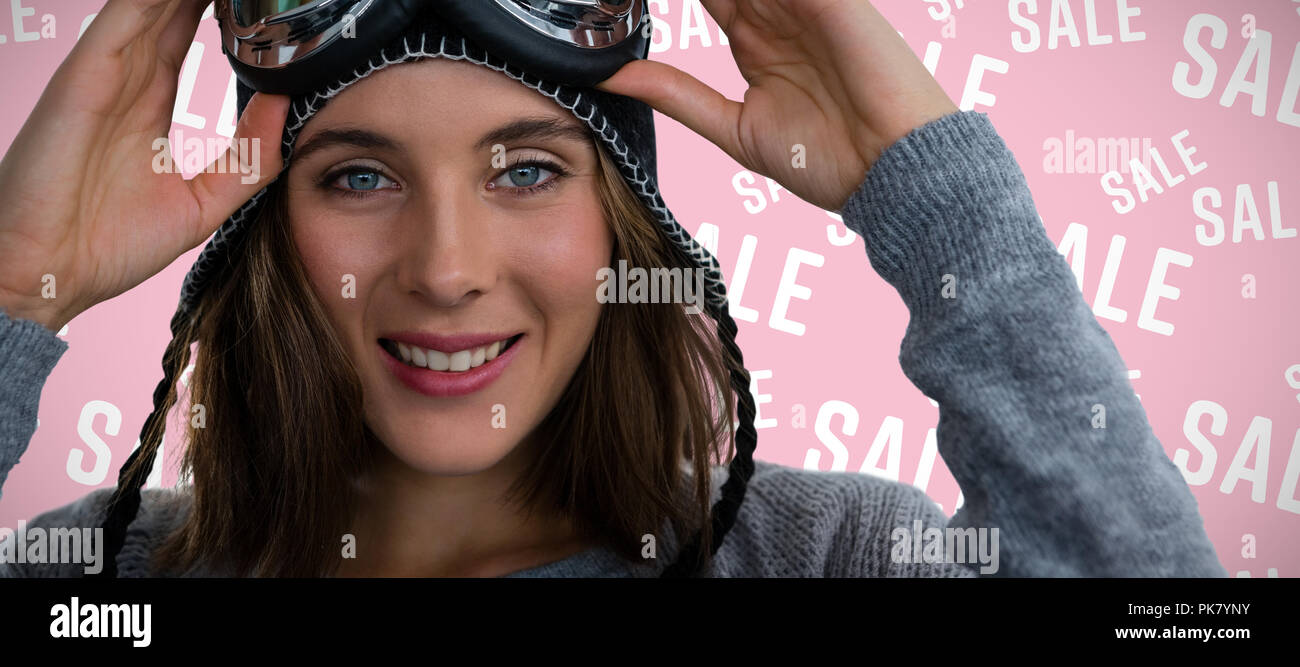 Composite image of portrait of woman with ski goggles - Stock Image