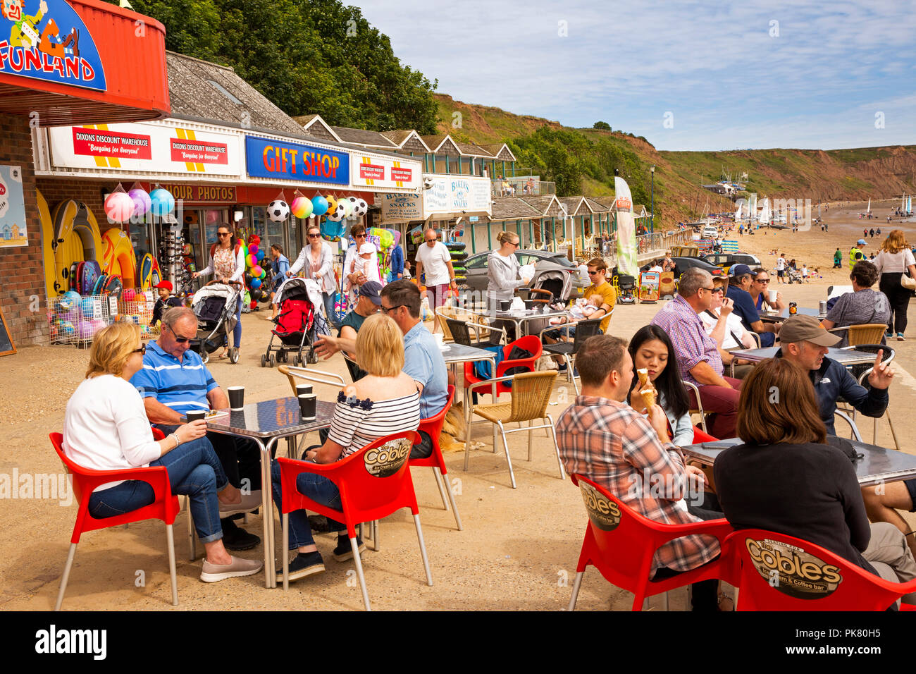 UK, England, Yorkshire, Filey, visitors at Coble Landing cafe tables in sunshine Stock Photo
