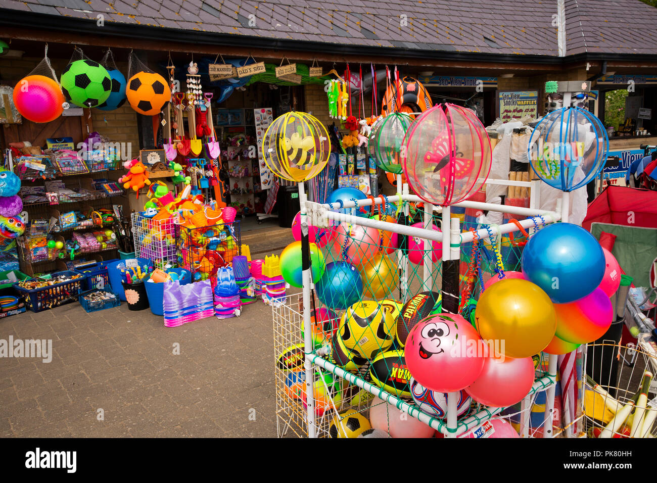 UK, England, Yorkshire, Filey, Coble Landing, colourful inexpensive beach toys outside shop - Stock Image