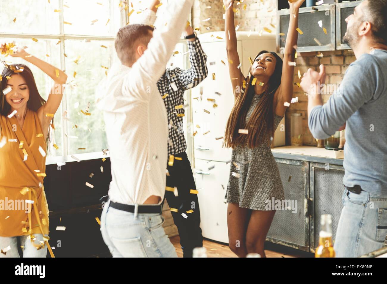 Confetti fun. Group of happy young people throwing confetti and jumping while enjoying home party on the kitchen. - Stock Image