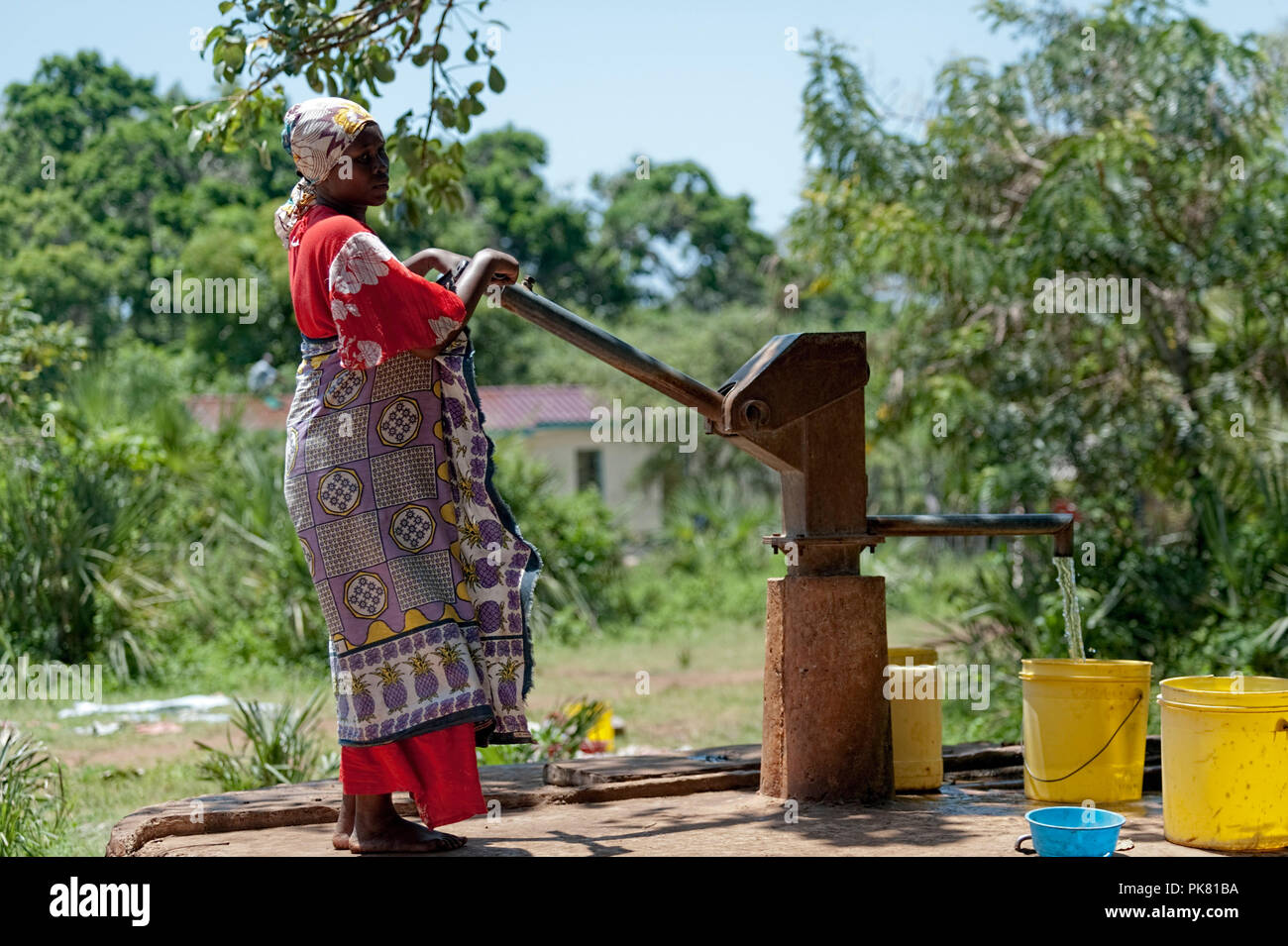 African Lady pumping water from well Funzi Island Kenya East Africa - Stock Image